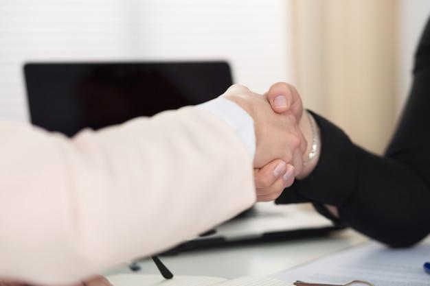 Рукопожатие двух женщин в офисе крупным планом. деловые женщины, пожимая руки. концепция серьезного бизнеса, партнерства и сотрудничества. Premium Фотографии