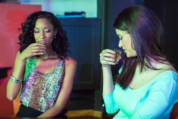 Two women having tequila at nightclub Premium Photo