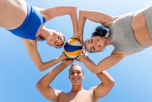 Due donne e un uomo in posa insieme alla pallavolo Foto Gratuite