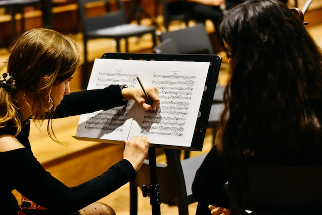Two women musicians correcting a score with a pencil before the orchestra begins to play. Premium Photo