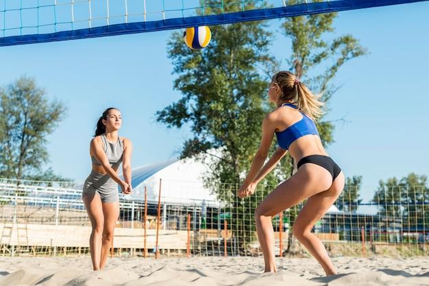 Due donne che giocano insieme a pallavolo sulla spiaggia Foto Gratuite