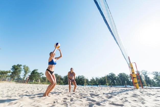 Due donne che giocano a pallavolo sulla spiaggia Foto Gratuite