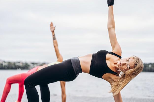 2人の女性が、水の近くの通りのマットでヨガの練習をします。アクティブなライフスタイル。ヨガのコンセプト Premium写真