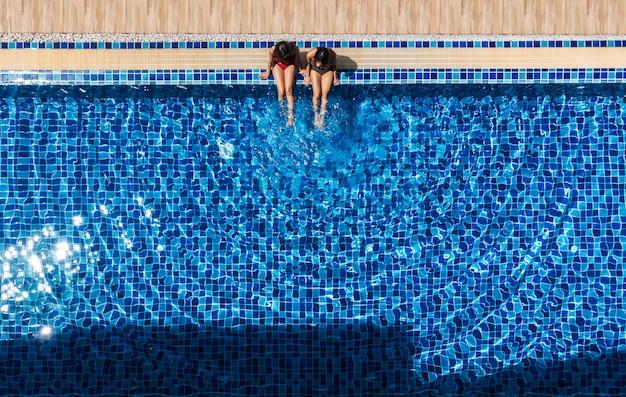 Две женщины расслабиться и сидеть у бассейна. Premium Фотографии
