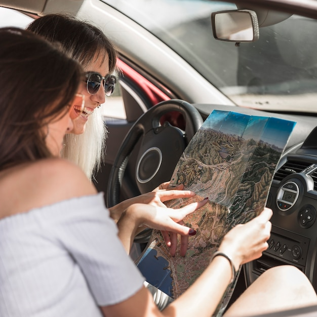 Two women sitting in car looking at map Free Photo