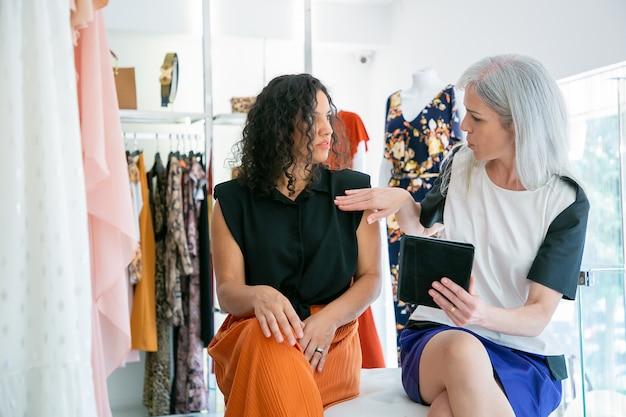 Две женщины сидят вместе и используют планшет, обсуждают одежду и покупки в магазине модной одежды. передний план. потребительство или концепция покупок Бесплатные Фотографии