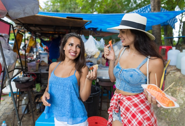 Two women tourists eat fresh fruits happy smiling walking streets Premium Photo