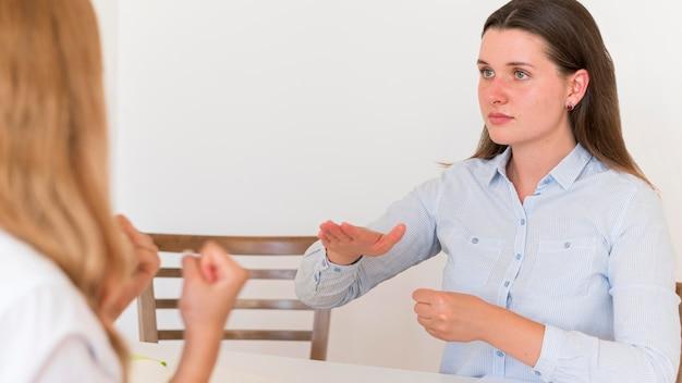 Две женщины используют язык жестов для общения за столом Бесплатные Фотографии