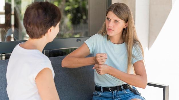 Две женщины используют язык жестов для общения друг с другом Бесплатные Фотографии