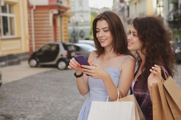Two women using smart phone, walking in the city after shopping together Premium Photo