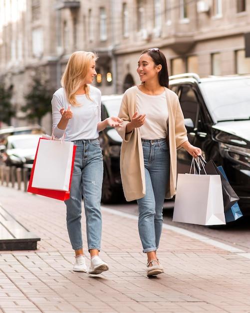 Две женщины гуляют по улице с сумками для покупок Бесплатные Фотографии