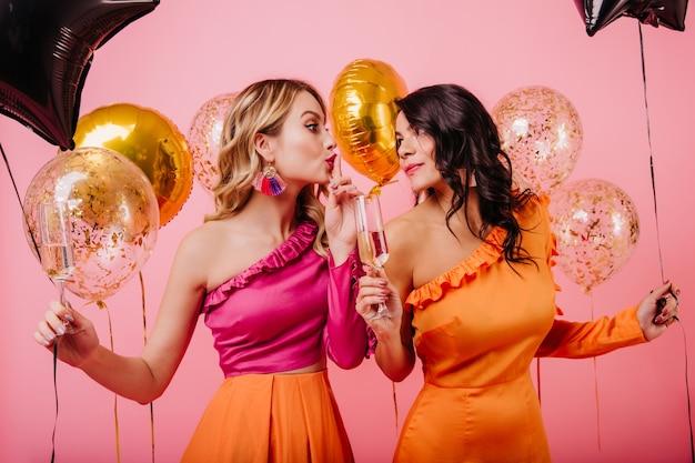 스파클 풍선 파티에서 얘기하는 두 여자 무료 사진
