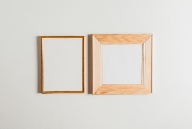 Two wooden frames hanging on white wall Photo | Free Download