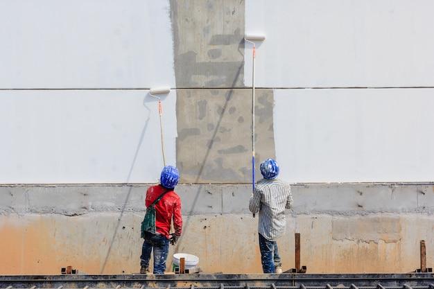 Два рабочих рисуют пустую область на стене Premium Фотографии