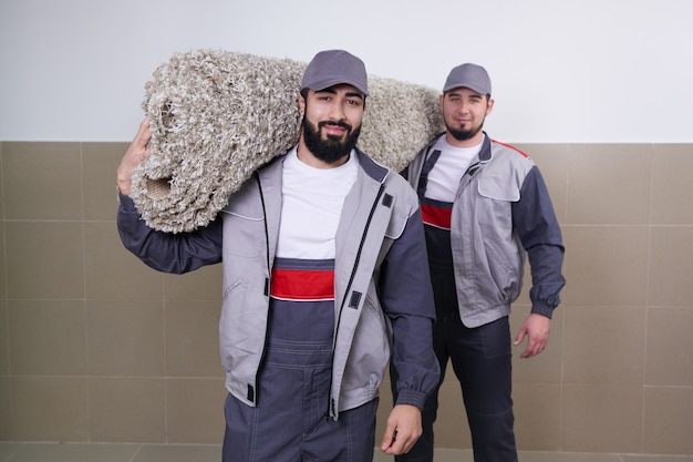 Two workers carrying big carpet after washing service Premium Photo