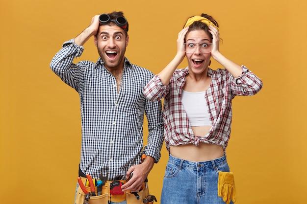 Двое работников сервисной службы позируют у желтой стены, возбужденно глядя, касаясь головами и крича с широко открытыми ртами. концепция ремонта, перепланировки и обновления Бесплатные Фотографии