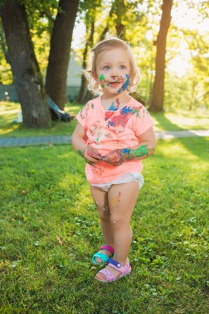 Ragazza di due anni macchiata a colori contro prato verde Foto Gratuite