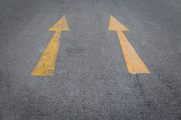 Two yellow arrows old and new  directionon asphalt road background Premium Photo