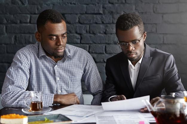 財務報告を検討する2人の若いアフリカ系アメリカ人幹部 無料写真