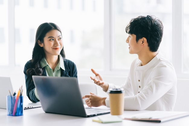Two young asian businessmen are discussing the year-end project Premium Photo