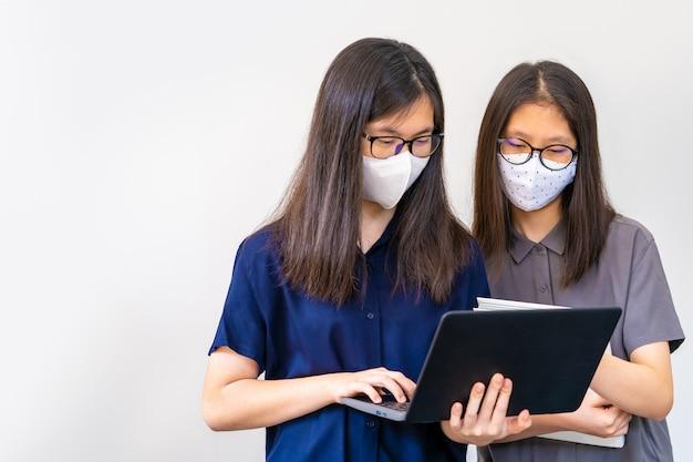 2人の若いアジアのティーンエイジャー、マスクを着用し、学校のプロジェクトで近づきすぎ Premium写真