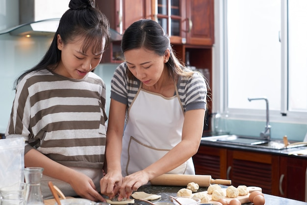 Two young asian women cutting out cookies from dough on kitchen counter Free Photo