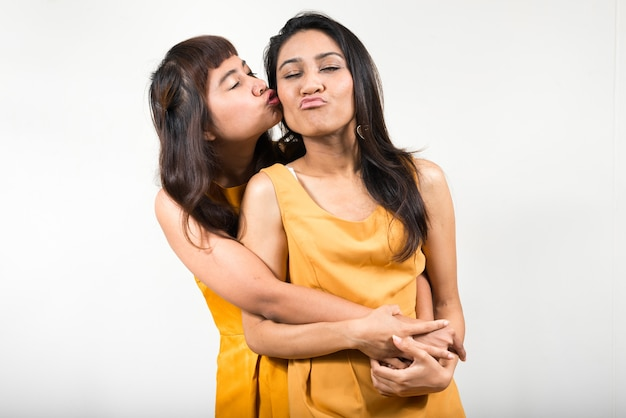 Two young asian women together against white space Premium Photo