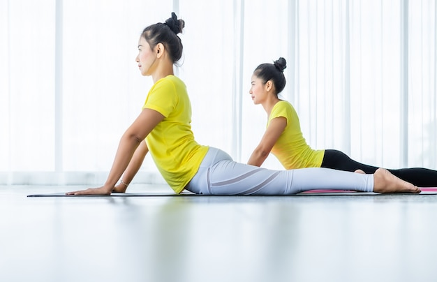 2人の若いアジア女性は黄色のドレスでヨガの練習をトレーニングまたはトレーナーとポーズし、瞑想ウェルネスライフスタイルと健康フィットネスの概念を練習 Premium写真