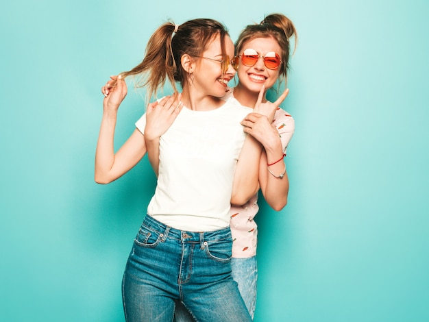Two young beautiful blond smiling hipster girls in trendy summer hipster jeans clothes. sexy carefree women posing near blue wall. trendy and positive models having fun in sunglasses Free Photo