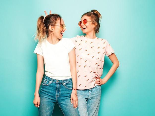 Due giovani belle ragazze sorridenti bionde dei pantaloni a vita bassa in vestiti d'avanguardia dei jeans dei pantaloni a vita bassa dell'estate. donne spensierate sexy che posano vicino alla parete blu. modelli alla moda e positivi che si divertono Foto Gratuite