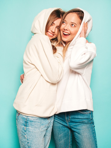 Free sexy girls in hood Free Photo Two Young Beautiful Blond Smiling Hipster Girls In Trendy Summer Hoodie Clothes Sexy Carefree Women Posing Near Blue Wall Trendy And Positive Models Having Fun