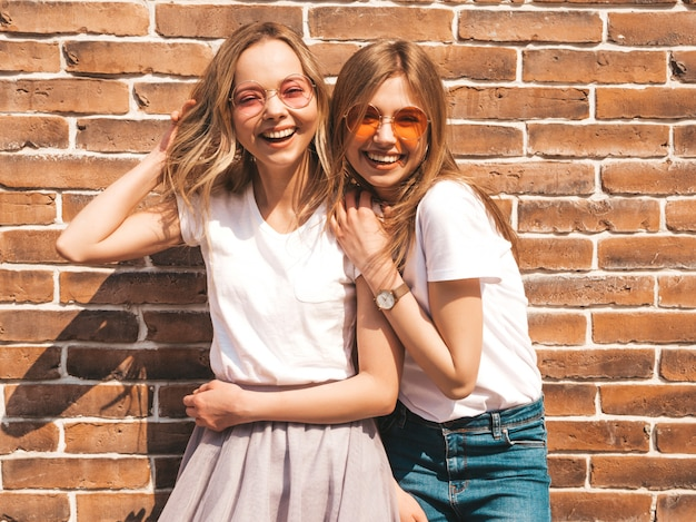 Two young beautiful blond smiling hipster girls in trendy summer white t-shirt clothes.  . positive models having fun in sunglasses Free Photo