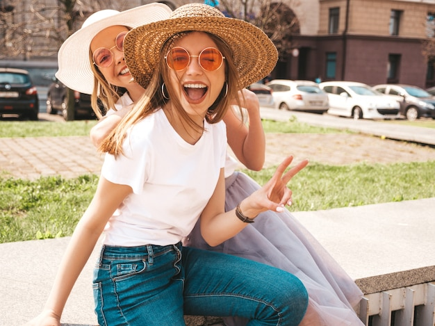 Two young beautiful blond smiling hipster girls in trendy summer white t-shirt clothes.  . . showing peace Free Photo