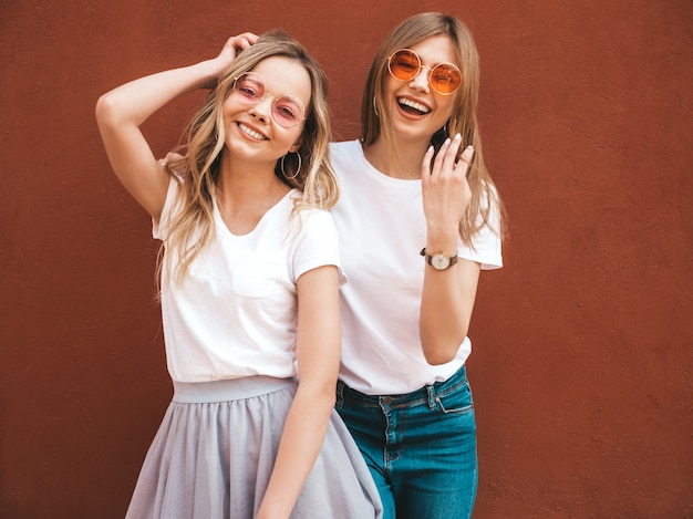 Two young beautiful blond smiling hipster girls in trendy summer white t-shirt clothes. women posing in the street near red wall. positive models having fun in sunglasses Free Photo
