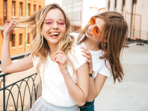 Two young beautiful blond smiling hipster girls in trendy summer white t-shirt clothes. women posing on street . positive models having fun in sunglasses.shows peace sign Free Photo