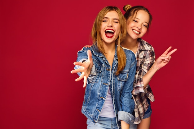Two young beautiful blond smiling hipster women posing in trendy summer checkered shirt clothes Free Photo