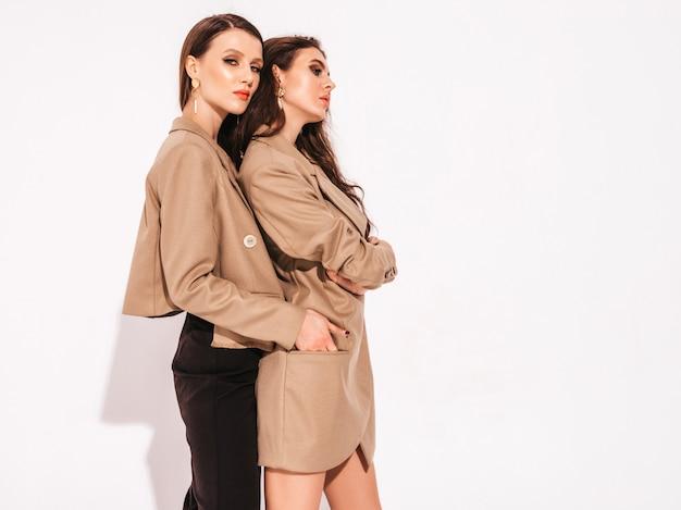 Две молодые красивые брюнетки в модных летних костюмах Бесплатные Фотографии