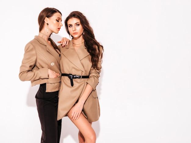 素敵なトレンディな夏の2つの若い美しいブルネットの女の子のスーツの服 無料写真
