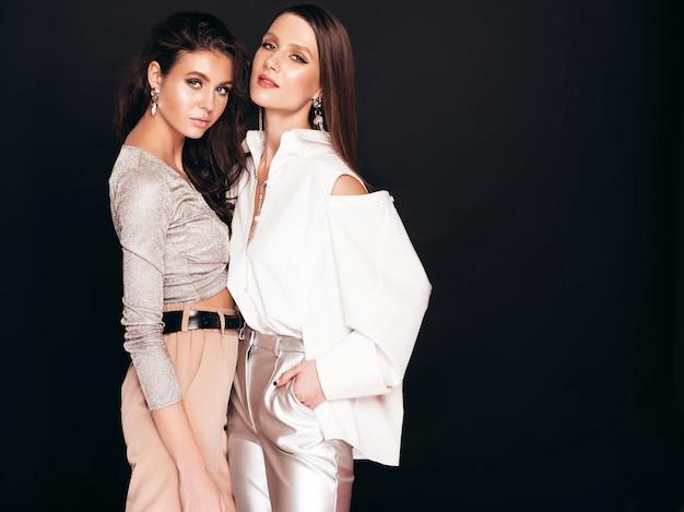 Due giovani belle ragazze castane in bei vestiti d'avanguardia di estate donne spensierate sexy che posano sopra il nero in studio Foto Gratuite