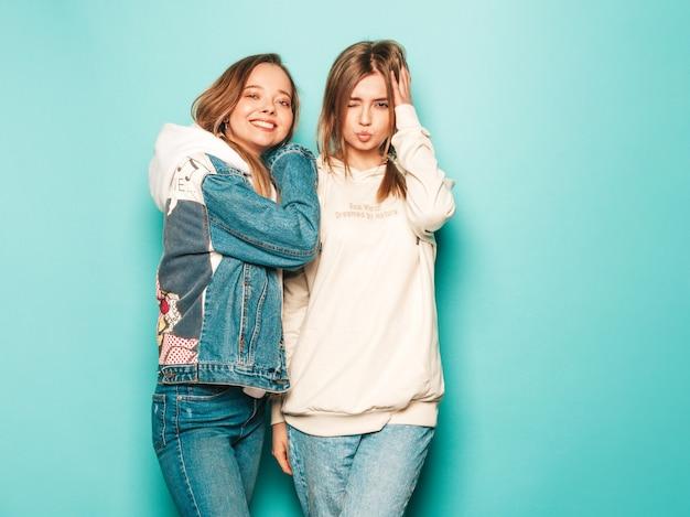 Две молодые красивые брюнетки улыбающиеся хипстерские девушки в модной летней толстовке и джинсовой куртке одеваются. сексуальные беззаботные женщины позируют возле синей стены. модные и позитивные модели с удовольствием Бесплатные Фотографии