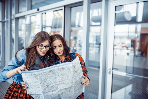 Two young beautiful girls are studying and looking at the map. Premium Photo