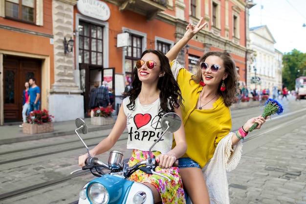 Две молодые красивые хипстерские женщины, едущие на мотоциклетной городской улице Бесплатные Фотографии