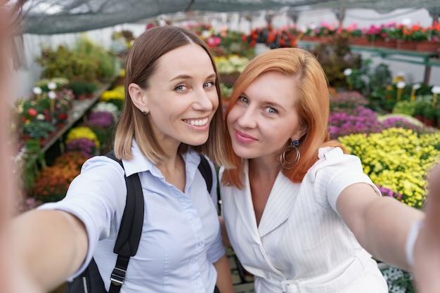 Две молодые красивые дамы делают селфи на фоне цветов в теплице Бесплатные Фотографии