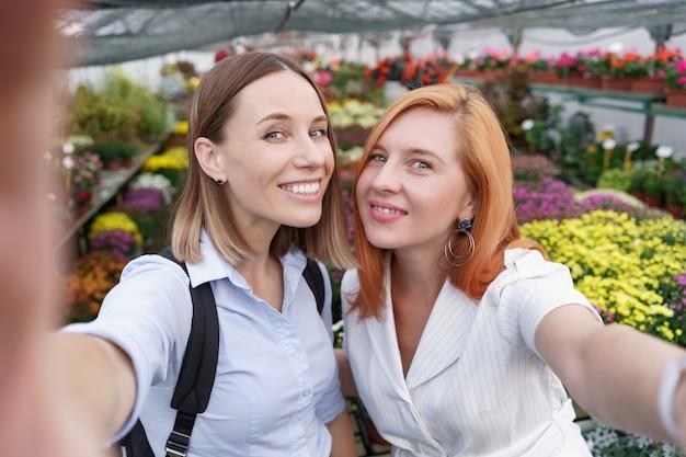 温室で花の背景に自分撮りを作る2人の若い美しい女性 無料写真