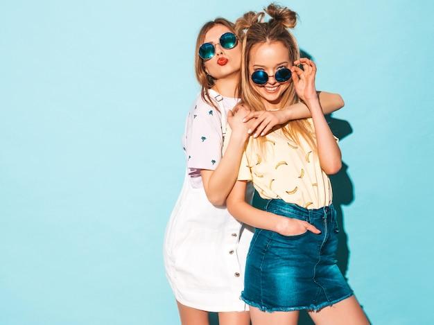 トレンディな夏のカラフルなtシャツの服の2人の若い美しい笑顔金髪流行に敏感な女の子。舌を見せて 無料写真