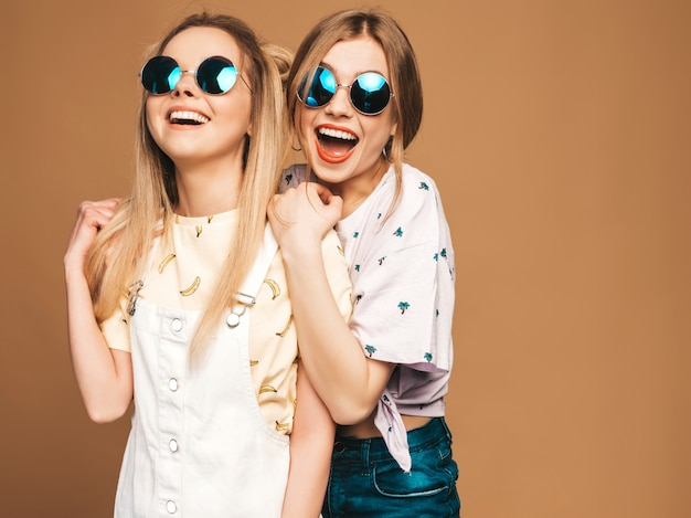 Two young beautiful smiling blond hipster girls in trendy summer colorful t-shirt clothes. sexy carefree women posing on beige background in round sunglasses. positive models having fun Free Photo