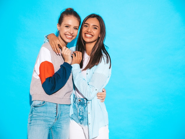 Two young beautiful smiling blond hipster girls in trendy summer colorful t-shirt clothes. sexy carefree women posing near blue wall. positive models having fun Free Photo