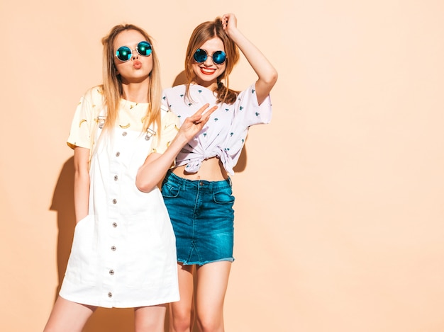 Two young beautiful smiling blond hipster girls in trendy summer colorful t-shirt clothes. Free Photo