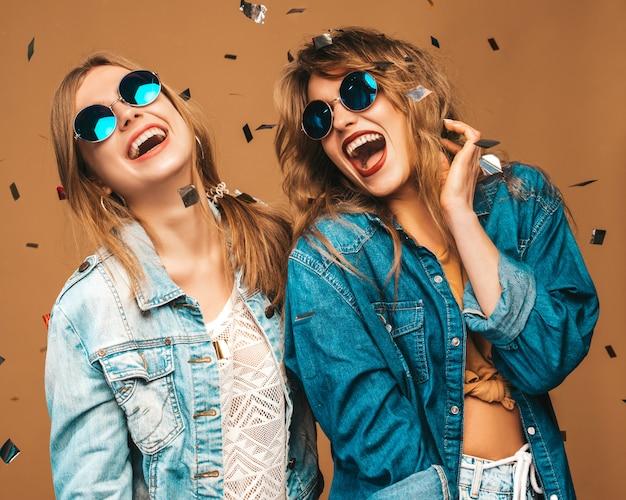 Две молодые красивые улыбающиеся девушки в модной летней одежде и солнцезащитные очки. сексуальные беззаботные женщины позируют. позитивные кричащие модели под конфетти Бесплатные Фотографии