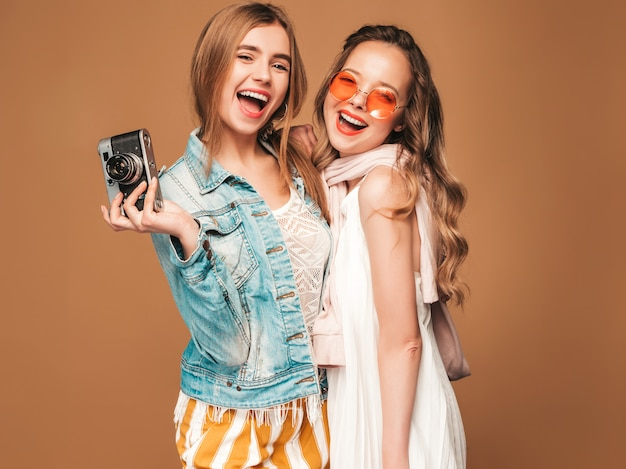Two young beautiful smiling girls in trendy summer casual clothes and sunglasses. sexy carefree women posing. taking pictures on retro camera Free Photo